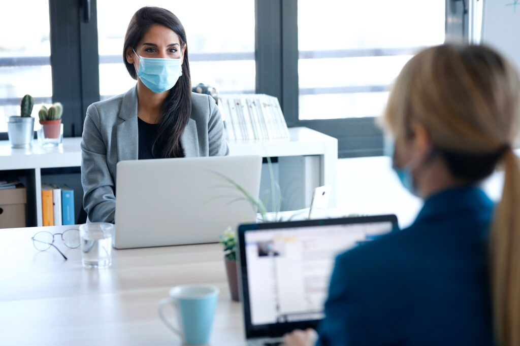 businesswomen wearing a hygienic face mask while working with laptops in the coworking space nearby